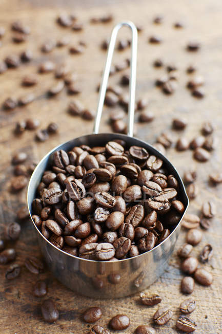 Measuring cup of coffee beans on dark wood — Stock Photo