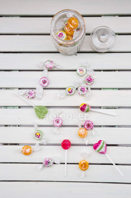 Top view of different lollipops on white wood — Stock Photo