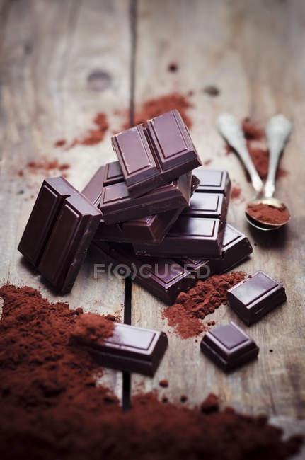Zartbitterschokolade mit Teelöffel und Kakaopulver auf Holz — Stockfoto