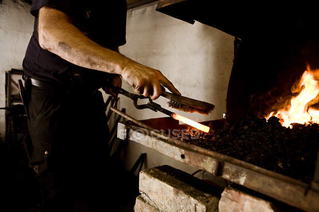 Blacksmith at work at the fireplace — Stock Photo