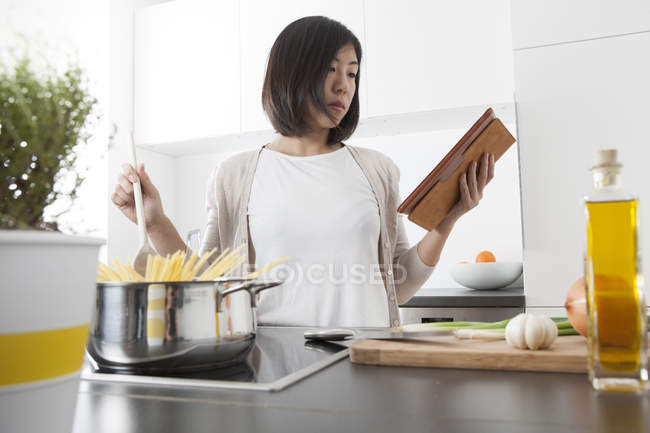 Молода жінка, використовуючи цифровий планшетний під час приготування спагетті — стокове фото