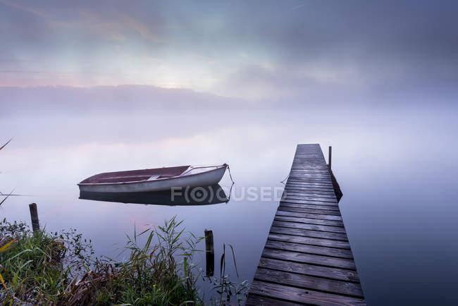 Alemania, Wessling, Wesslinger Ver, barco y pasarela de madera en la niebla de la mañana - foto de stock