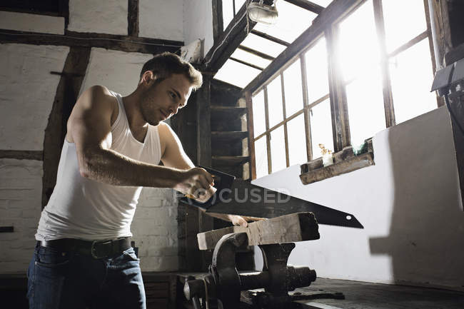 Young man sawing wooden beam in front of his half-timbered house at night — Stock Photo