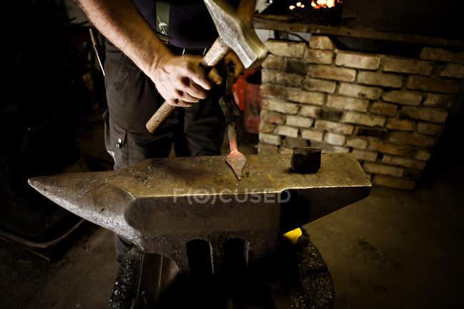 Вироби ковальські роботи з молотка на ковадлі, крупним планом подання чоловічої руки — стокове фото