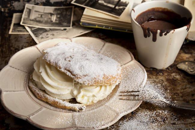 Panino riempito con panna montata, tazza di cioccolato caldo — Foto stock