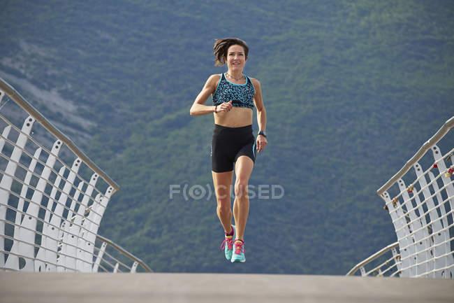 Женщина бегает по мосту — стоковое фото
