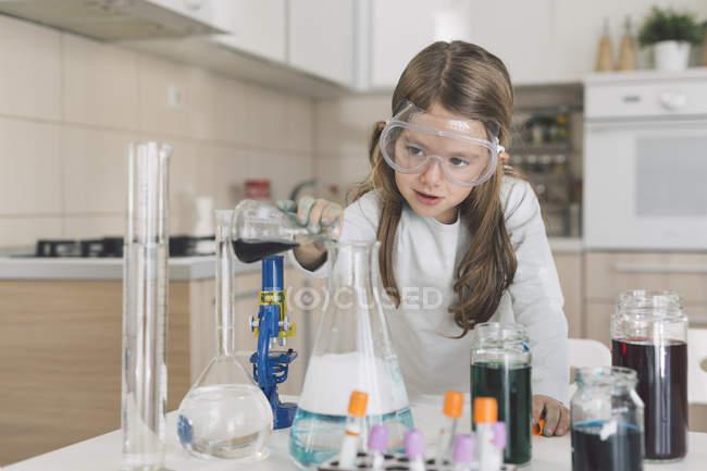 Девочка играет в научные эксперименты на дому — стоковое фото