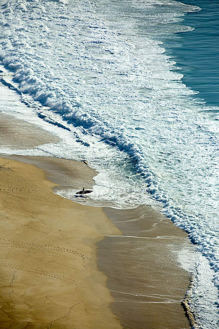 Portugal, Nazare, man standing with paddleboard on beach — Stock Photo