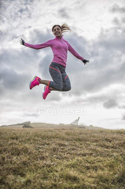 81b615f42846ac Sportliche junge Frau, die springen auf der Wiese — Stockfoto