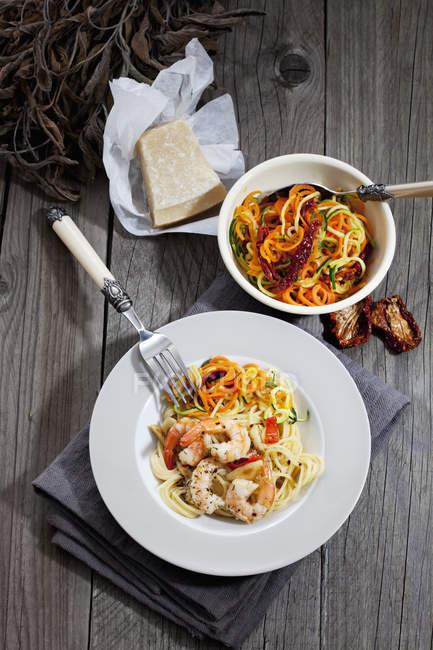 Spaghetti mit Scampis und Gemüse auf Teller, Schüssel mit Tomatenspiralen und Zucchini, getrocknete Tomaten — Stockfoto