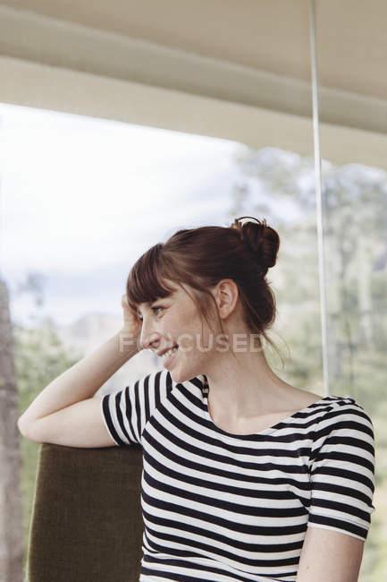 Lächelnde Frau vor der Fensterscheibe — Stockfoto
