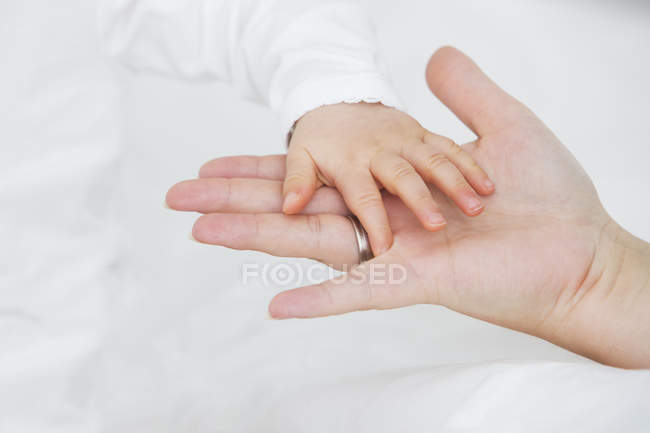 Baby girl's hand on mother's hand — Stock Photo