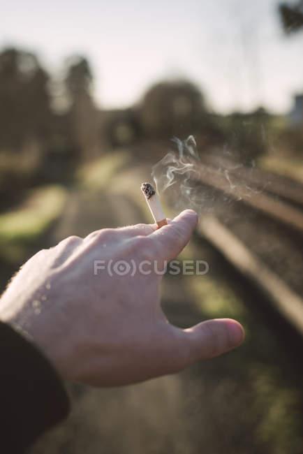 Крупный план мужской руки, держащей сигарету — стоковое фото
