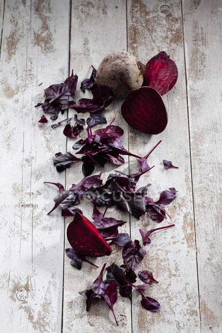 Sliced and whole beetroots with leaves — Stock Photo
