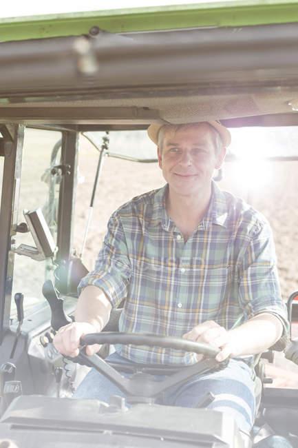 Fermier souriant conduisant au tracteur — Photo de stock