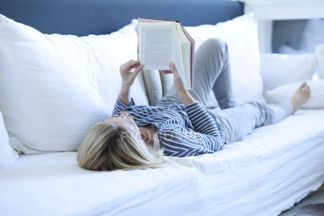 Femme allongée sur le canapé lisant un livre — Photo de stock
