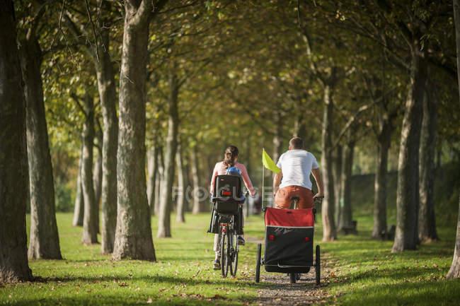 Famille de bicyclettes à cheval sur le chemin d'accès au parc — Photo de stock