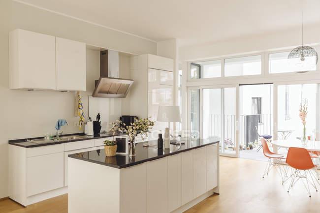 Cozinha com ilha de balcão e mesa no interior do edifício moderno — Fotografia de Stock