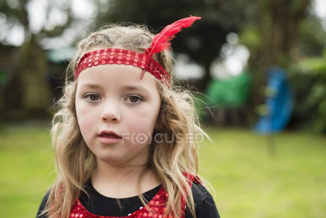 Ritratto di bambina con fascia rossa e piuma — Foto stock