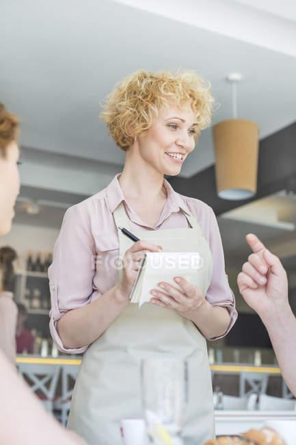 Camarera en una cafetería tomando la orden - foto de stock