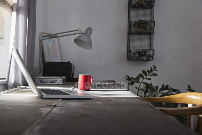 Desk with laptop and coffee cup at home office — Stock Photo
