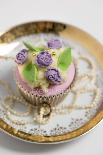 Cupcake with rose blossom fondant and butter cream on vintage plate — Stock Photo
