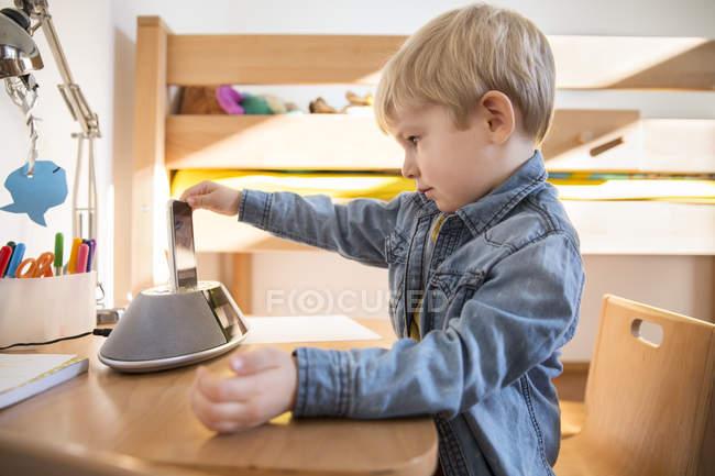 Маленький мальчик, использующий MP3-плеер и док-станцию для прослушивания музыки в его нузерах — стоковое фото