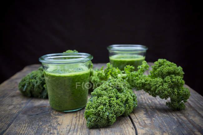 Два стакана капустного смузи на деревянной поверхности — стоковое фото