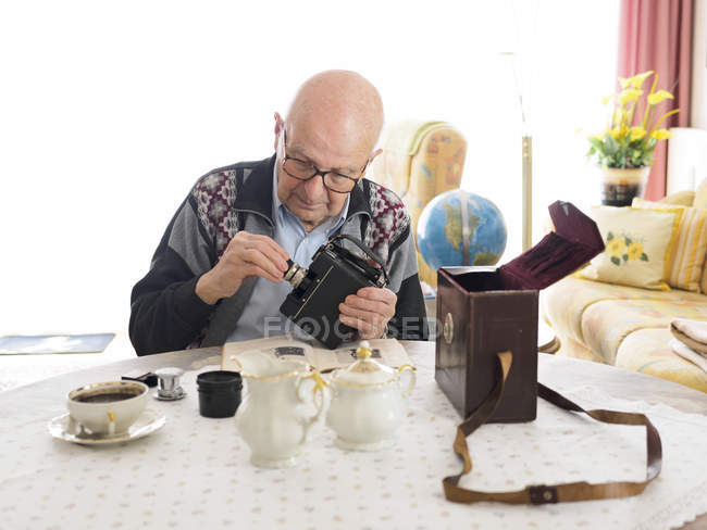 Old man sitting at table and dealing with old camera — Stock Photo