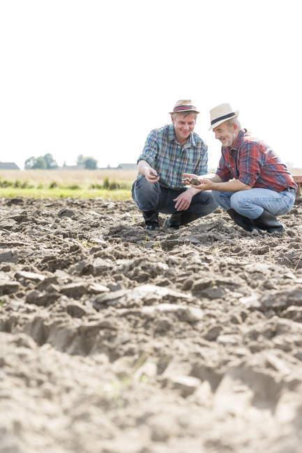 Deux agriculteurs examinant sol dans domaine — Photo de stock