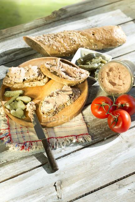Крупним планом ліверна ковбаса, поширення з маринованими огірками та помідорами на дерев'яні таблиці — стокове фото