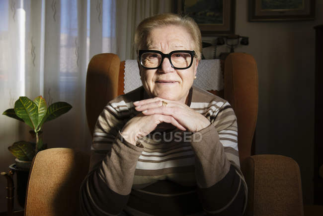 Portrait of happy elderly lady sitting on the armchair — Stock Photo