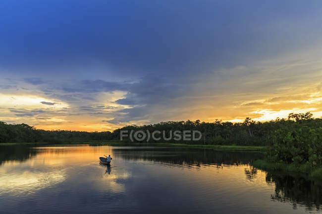 Ecuador, región del río Amazonas, canoa dugout en el lago Pilchicocha al atardecer - foto de stock