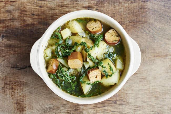 Nahaufnahme der Schüssel mit portugiesischen Caldo Verde mit Kartoffeln, Wirsing und vegane Würstchen — Stockfoto