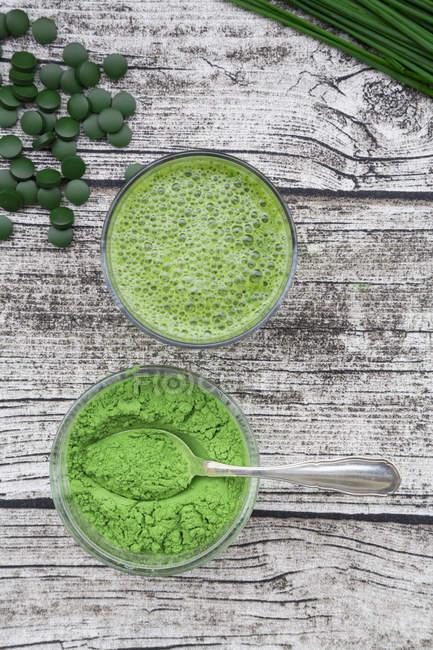 Copo de suco de wheatgrass e tigela de pó de wheatgrass — Fotografia de Stock