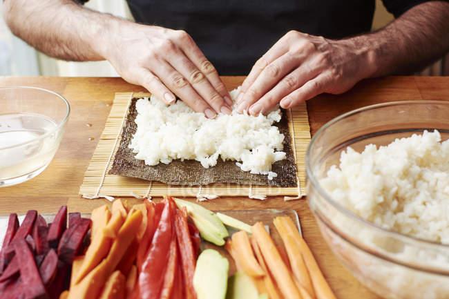 Männliche Hände ausbreitende Reis auf einem Nori-Blatt, pflanzliche Sushi zu machen — Stockfoto