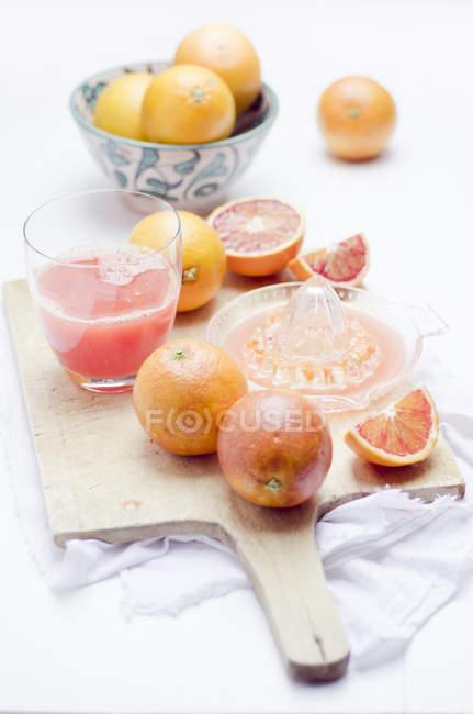 Nahaufnahme von Glas mit frisch gepresstem roten Orangensaft und roten Orangen auf Holzbrett — Stockfoto