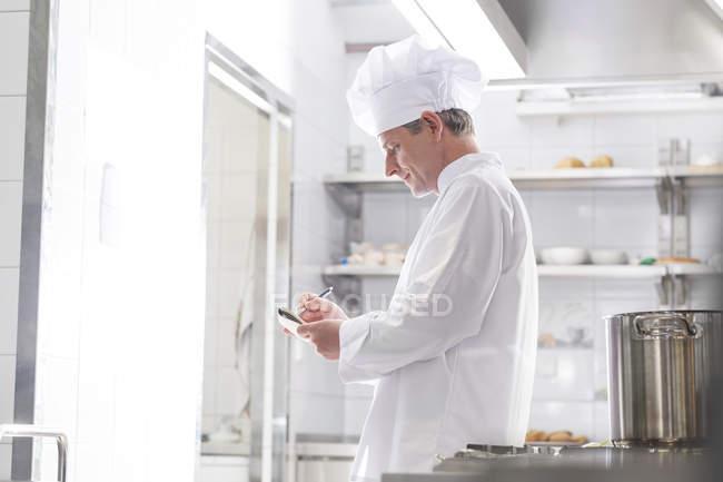 Chef en cuisine, prendre des notes, vue latérale — Photo de stock