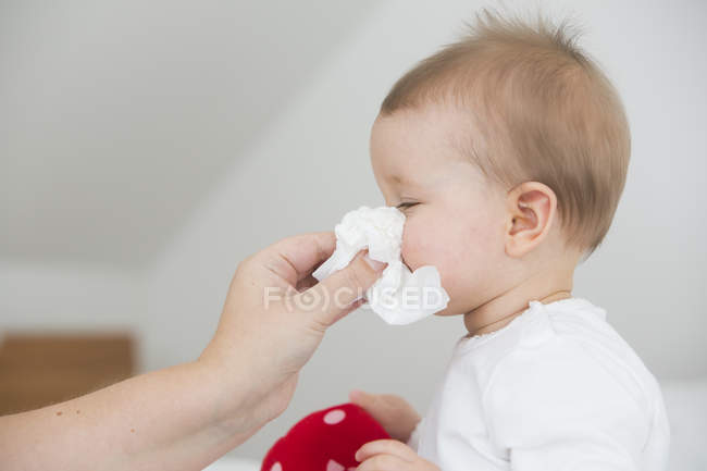 Mother blowing baby girl's nose — Stock Photo