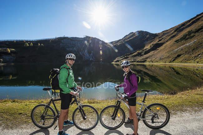 Pareja joven de Austria, Altenmarkt-Zauchensee, con bicicletas de montaña en el lago de la montaña - foto de stock
