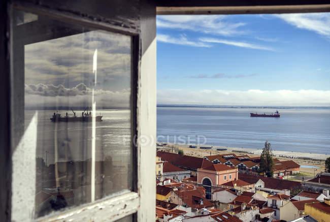 Blick auf alfama viertel und fluss tejo durch offenes fenster, lisbon, portugal — Stockfoto