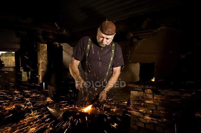 Коваль, працює з молотом на ковадлі оточенні іскри — стокове фото