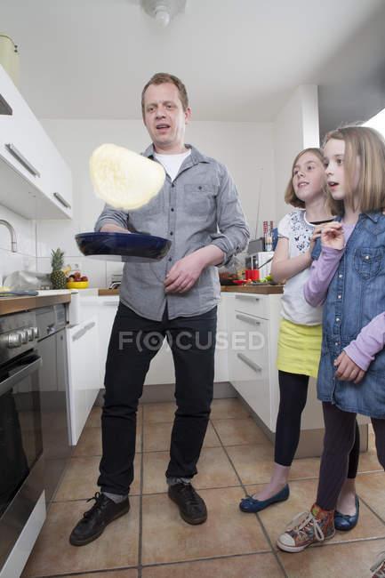 Человек готовит блины с дочерьми на кухне — стоковое фото