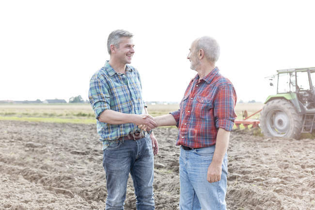 Two farmers on field shaking hands, tractor on background — Stock Photo
