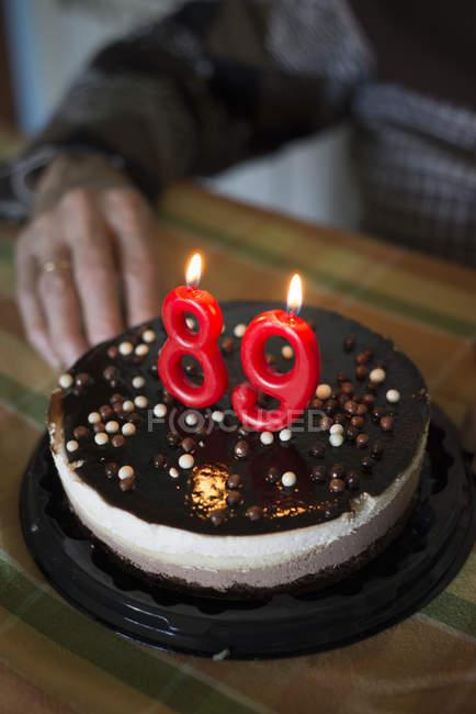 Старуха празднует 89-летие с праздничным тортом на переднем плане — стоковое фото