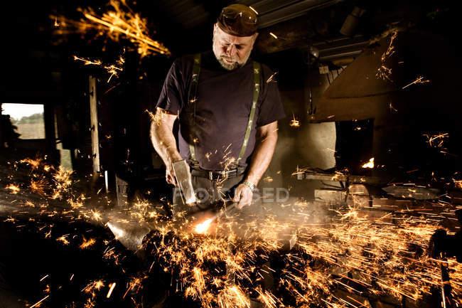 Кузнец, работающий с молотком на наковальне, окруженный искрами — стоковое фото