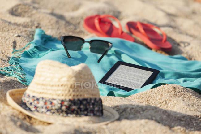 Рушник, сонцезахисні окуляри, шльопанці, солом'яний капелюшок і Цифрова табличка на піщаний пляж — стокове фото