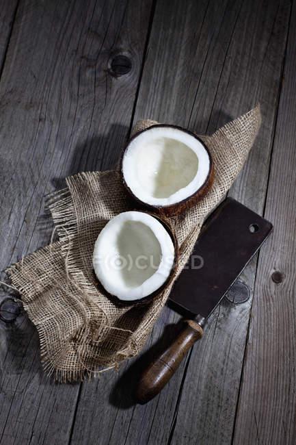 Coco dividido em hessiano e velho cutelo — Fotografia de Stock
