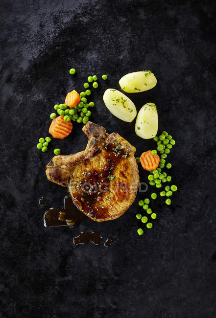 Côtelette de porc avec carottes, petits pois et pommes de terre bouillies — Photo de stock