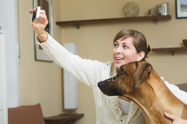 Жінка, беручи selfie зі своїм собакою родезійськими ріджбек — стокове фото
